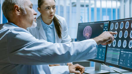 Two Medical Scientists in the Brain Research Laboratory Discussing Progress on the Neurophysiology Project Curing Tumors. Neuroscientists Use Personal Computer with MRI, CT Scans Show Brain Images. Imagens