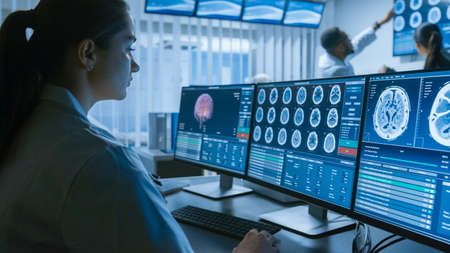 Over the Shoulder Shot of Female Medical Scientist Working with CT Brain Scan Images on a Personal Computer in Laboratory. Neurologists in Research Center Work on Brain Tumor Cure.