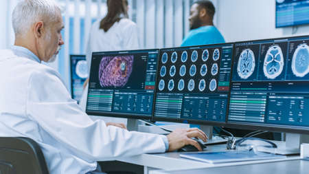 Experienced Senior Scientist Working with CT MRI Brain Scan Images on a Personal Computer in Laboratory. Neurologists Neuroscientists in Medical Research Center Work on Brain Tumor Cure.
