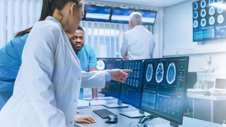 Diverse Team of Medical Scientists Solve Problems and Point at Computer Screens Showing CT, MRI Scans. Neurologists Neuroscientists Working in Brain Research Laboratory. Stock Photo
