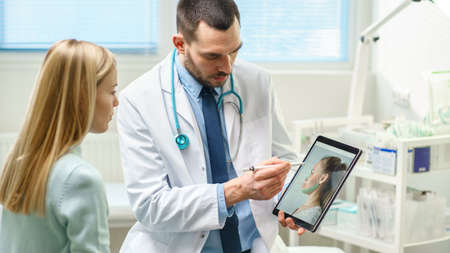 Plastic Cosmetic Surgeon Consults Woman about Facial Lift Surgery, He Draws Arrows on Digital Tablet Computer Screen, Showing Types of Facelift, Forehead Correcting Procedures Available for Her.