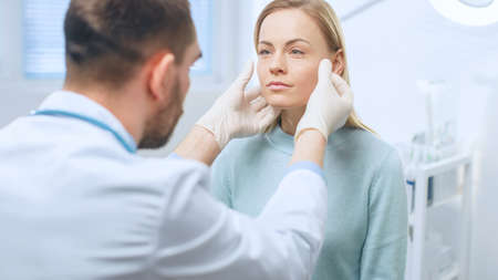 Plastic Cosmetic Surgeon Examines Beautiful Womans Face, Touches it with Gloved Hands, Inspecting Healed Face after Plastic Surgery with Amazing Results.