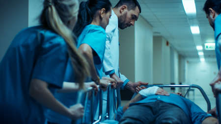 Emergency Department: Doctors, Nurses and Surgeons Move Seriously Injured Patient Lying on a Stretcher Through Hospital Corridors. Medical Staff in a Hurry Move Patient into Operating Theater. Stock fotó