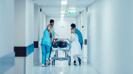 Emergency Department: Doctors, Nurses and Paramedics Push Gurney Stretcher with Seriously Injured Patient towards the Operating Room. Bright Modern Hospital with Professional Staff Saving Lives.