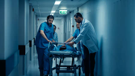 Emergency Department: Doctors, Nurses and Paramedics Run and Push Gurney Stretcher with Seriously Injured Patient towards the Operating Room. Modern Hospital with Professional Staff.