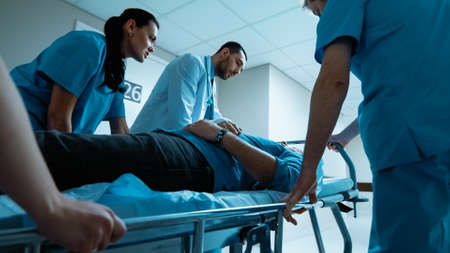 Emergency Department: Doctors, Nurses and Paramedics Run and Push Gurney Stretcher with Seriously Injured Patient towards the Operating Room. Bright Modern Hospital with Professional Staff.