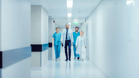 Team of Doctors, Surgeons and Nurses Walk Through Busy Hospital Hallway, They Talk about Patients, Forthcoming Surgeries and Saving Lives. Clean Modern Hospital with Professional Staff. Standard-Bild