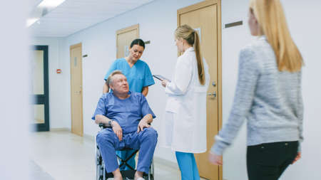 In the Hospital Hallway, Nurse Pushes Elderly Patient in the Wheelchair, Doctor Talks to Them while Using Tablet Computer. Clean, New Hospital with Professional Medical Personnel.