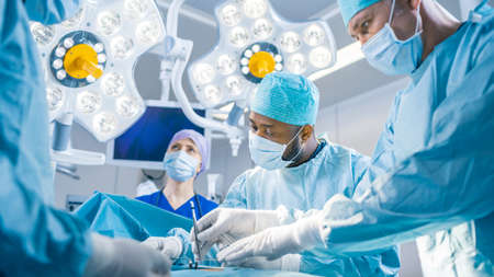 Diverse Team of Professional surgeon, Assistants and Nurses Performing Invasive Surgery on a Patient in the Hospital Operating Room. Surgeons Talk and Use Instruments. Real Modern Hospital with Reklamní fotografie