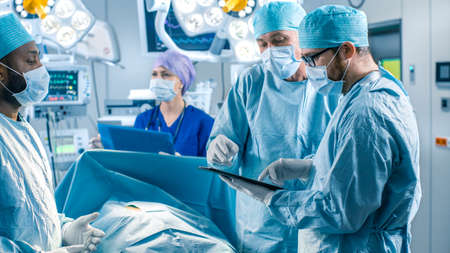 Professional Surgeons and Assistants Talk and Use Digital Tablet Computer During Surgery. They Work in the Modern Hospital Operating Room.