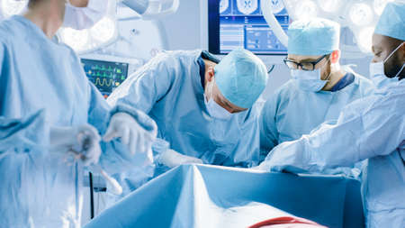 Diverse Team of Professional surgeon, Assistants and Nurses Performing Invasive Surgery on a Patient in the Hospital Operating Room. Real Modern Hospital with Authentic Equipment. Stock fotó