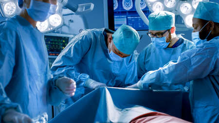 Diverse Team of Professional surgeon, Assistants and Nurses Performing Invasive Surgery on a Patient in the Hospital Operating Room. Real Modern Hospital with Authentic Equipment. Stockfoto