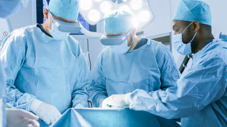Surgeons Wearing Augmented Reality Glasses Perform State of the Art Mixed Reality Surgery in High Tech Hospital. Doctors and Assistants Working in Operating Room.