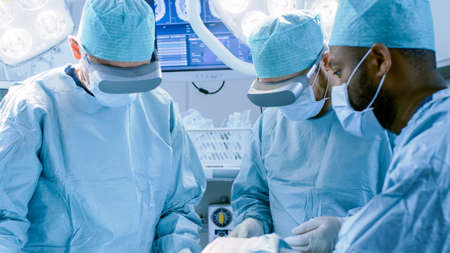 Surgeons in Augmented Reality Glasses Perform State of the Art Surgery in High Tech Hospital. Doctors and Assistants Working in Operating Room.