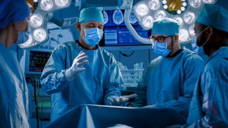 Diverse Team of Professional Doctors Performing Invasive Uses Augmented Reality Technology on a Patient in the Hospital Operating Room. Real Modern Hospital with Authentic Equipment.