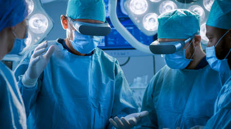 Surgeons Wearing Augmented Reality Glasses Perform State of the Art Augmented Reality Surgery in High Tech Hospital. Doctors and Assistants Working in Operating Room. Stock fotó