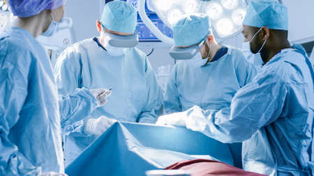 Surgeons Wearing Virtual Reality Glasses to Perform State of the Art Surgery in Technologically Advanced Hospital. Doctors and Assistants Working in Operating Room.