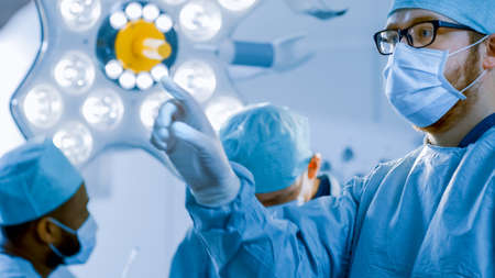 In the Operating Room Surgeon Gestures Using Augmented Reality Technology During Operation. In the Background Assistants and Nurses Working with Real Equipment. Stock fotó