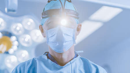 In the Hospital Operating Room Professional Surgeon With Surgical Flashlight Looks into Camera. Stock fotó