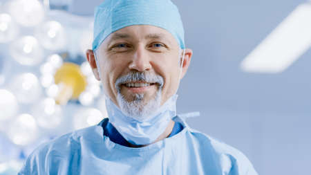 Portrait of the Professional Surgeon Takes off Surgical Mask after Successful Operation Simling Into Camera. In the Background Modern Hospital Operating Room.