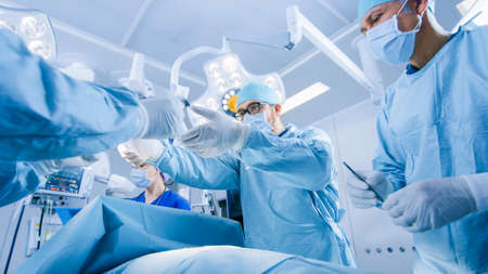 Low Angle Shot of a Diverse Team of Professional Surgeons Performing Invasive Surgery on a Patient in the Hospital Operating Room. Surgeons Use Instruments