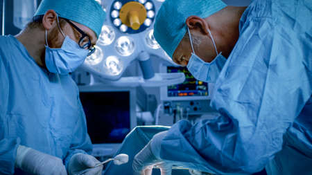 In the Hospital Operating Room Diverse Team of Professional Surgeons and Nurses Suture Wound after Successful Surgery.