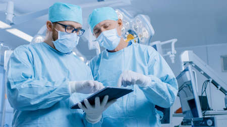 Two Professional Surgeons Use Digital Tablet Computer while Standing in the Modern Hospital Operating Room. Stock fotó
