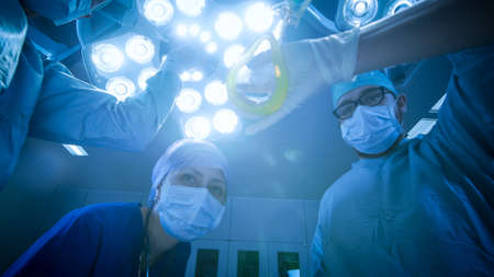 Low Angle Shot of Two Professional Surgeons Turning on Surgery Lights while Bending over Patient. POV Patient Shot in Modern Hospital Operating Room.