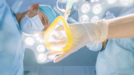 Low Angle Shot POV Patient View: Two Professional Surgeons Holding Surgical Instruments Ready to Operate.