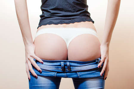 stripping: closeup picture of sensual hot buttocks in white lace underwear. slim fitness young woman standing in jeans having fun posing showing her excellent shape bum on light  Stock Photo