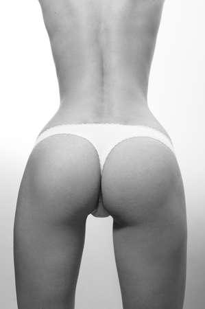 cuerpo femenino perfecto: gl�teos perfectos: muchacha de la aptitud delgado con excelente culo divertirse posando en ropa interior blanca que se coloca de nuevo a la c�mara en espacio de la copia gris Foto de archivo