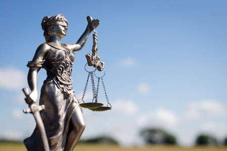 orden judicial: escultura de Themis, femida o diosa justicia sobre fondo brillante cielo azul