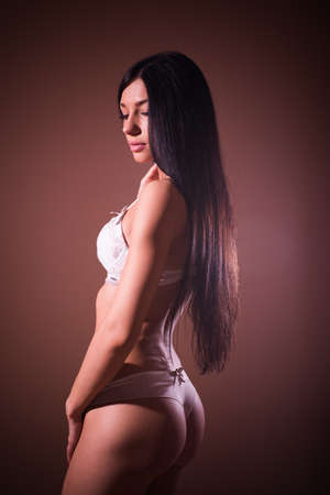 elegant buns: gorgeous sexy lady black hair glamor pinup girl with excellent fitness bum happy posing relaxing standing half back to camera & looking down shy on copy space background portrait image photo