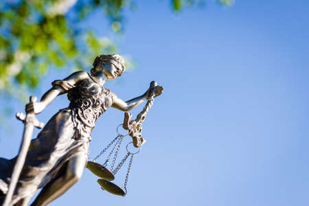 outdoors image of themis sculpture, femida or justice goddess on bright blue sky background