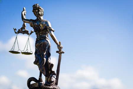 femida: picture of themis, femida or justice goddess sculpture on bright blue sky background