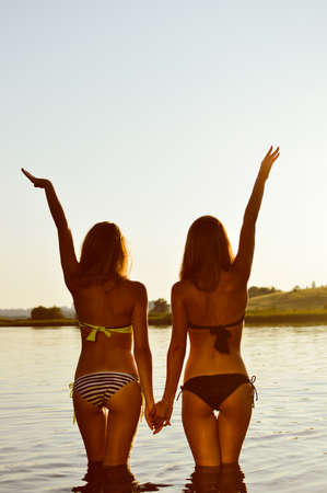 string bikini: 2 sexy pretty girls best girlfriends in bikini having fun together holding hands up to sky on summer sunset outdoors copy space background
