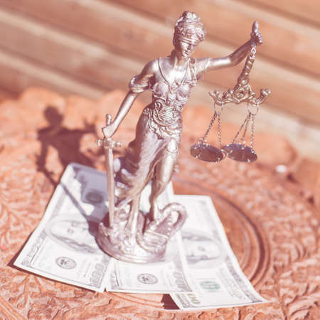 money and justice: sculpture of themis, femida or justice goddess standing on money bribe symbol of corruption Stock Photo