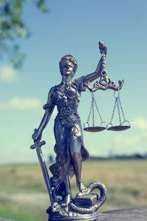 sculpture of themis, femida or justice goddess on bright blue sky outdoors copyspace background photo
