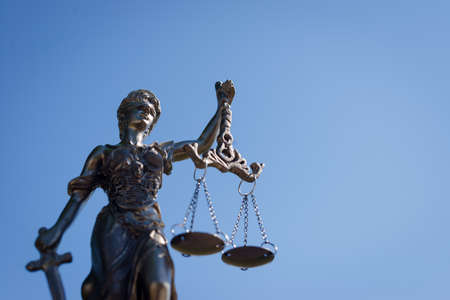 lady justice: sculpture of themis, femida or justice goddess on bright blue sky background