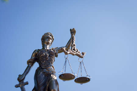 femida: sculpture of themis, femida or justice goddess on bright blue sky background