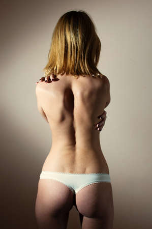 perfect buttocks: slim fitness girl with excellent butt having fun posing in white underwear standing back to camera on gray copy space background, closeup picture photo