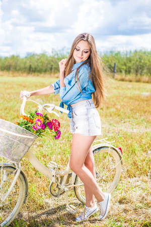time for cycling fun: portrait of beautiful brunette young woman having fun relaxing with bicycle on summer green field and blue sky outdoors copy space photo