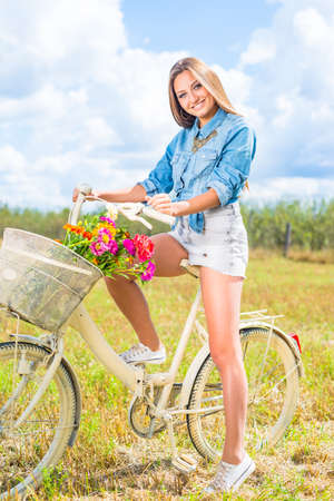 cycling fun: portrait of beautiful brunette young woman having fun relaxing with bicycle on summer green outdoors copy space photo