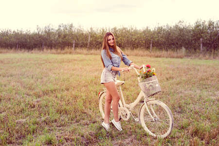 happy cycling time: portrait of beautiful brunette young woman having fun with bicycle on green summer outdoors copy space background photo
