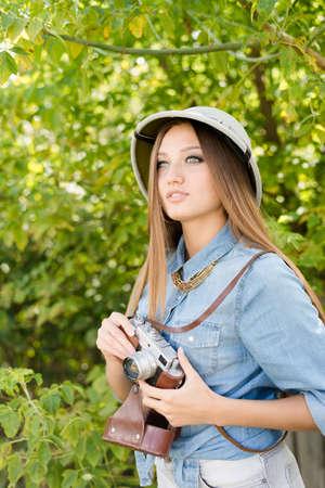 médula: Mujer hermosa joven en el sombrero de médula a tomar fotografías en la cámara retro de los árboles verdes de fondo copia espacio verano