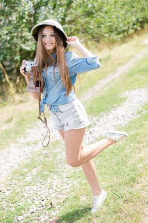 médula: Mujer hermosa joven en el sombrero de médula a tomar fotografías en la cámara retro en los árboles verdes de fondo copia espacio verano Foto de archivo
