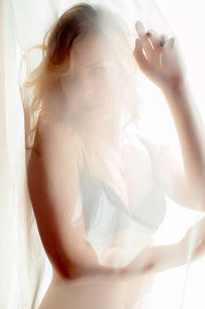 undies: portrait of blond happy pretty lady having fun hiding in bikini or undies & relaxing looking at camera on window light copy space background