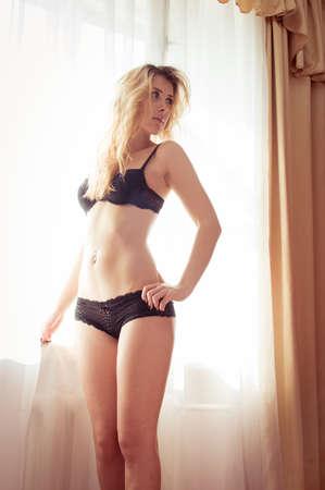 mujeres eroticas: sensual elegante hermosa dama sexy divertirse posando despojar desnudarse mostrando su cuerpo en forma de fitness perfecto en luz de la ventana de copia imagen de fondo del espacio