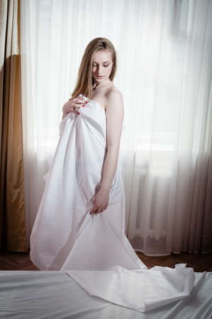 portrait of blond young beautiful woman having fun hiding under white sheet standing on light window copy space background photo