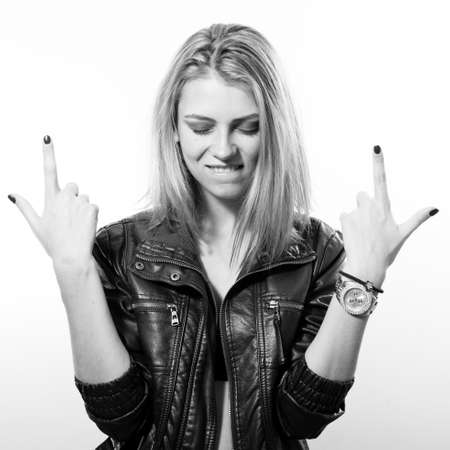 fashion rock star: black and white portrait of sexy young blonde woman in leather jacket posing happy smiling over light copy space background
